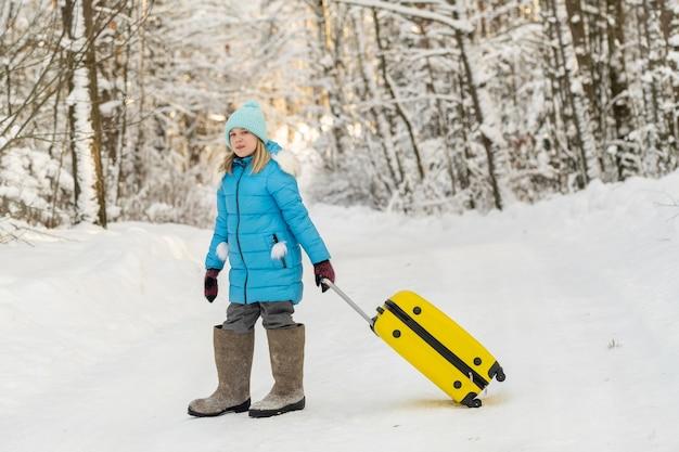 Une fille en hiver en bottes de feutre va avec une valise un jour de neige glacial