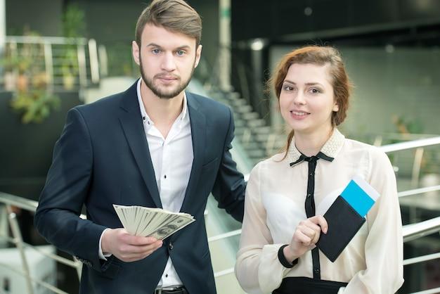Une fille et un homme tiennent des billets dans leurs mains.
