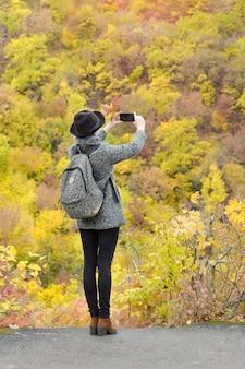 Fille avec des images de téléphone portable de la forêt d'automne. vue arrière