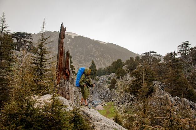 Fille à l'imperméable avec une capuche qui monte le rocher avec sac à dos de randonnée et bâtons
