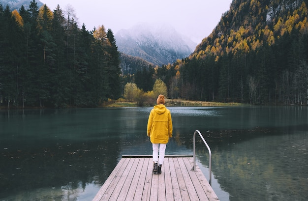 Fille en imperméable jaune regardant le lac de montagne à jezersko. voyage d'aventure en slovénie. automne ou hiver en europe. la femme se tient sur le pont en bois sur le fond de nature avec les alpes. style de vie de la liberté.