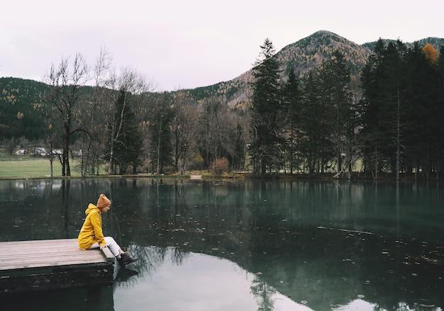 Fille en imperméable jaune regardant le lac de montagne à jezersko voyage d'aventure en slovénie