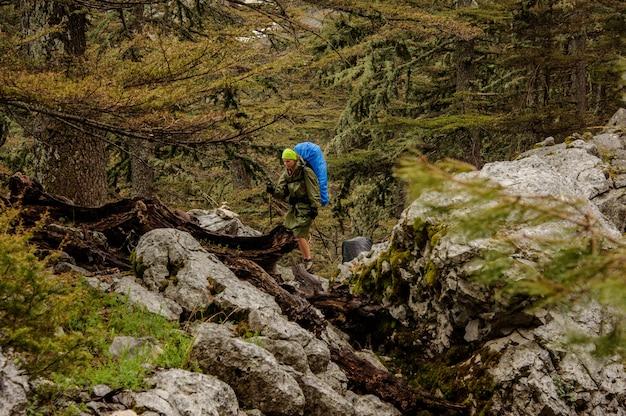 Fille à l'imperméable marchant sur les rochers avec sac à dos et bâtons de randonnée