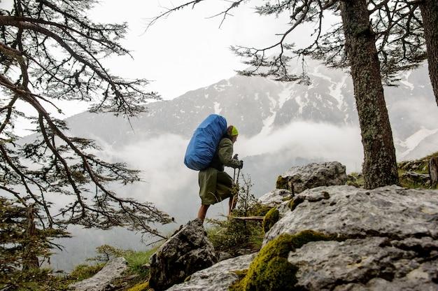 Fille à l'imperméable marchant sur les rochers avec sac à dos de randonnée bleu et bâtons