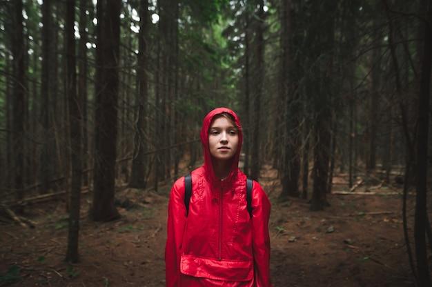 Fille en imperméable rouge et capuche se tient le soir dans la forêt sur le sentier et regarde ailleurs
