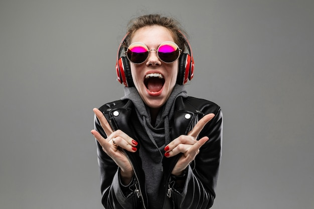 Fille impudente souriante écoute de la musique dans des écouteurs rouges sur un mur gris