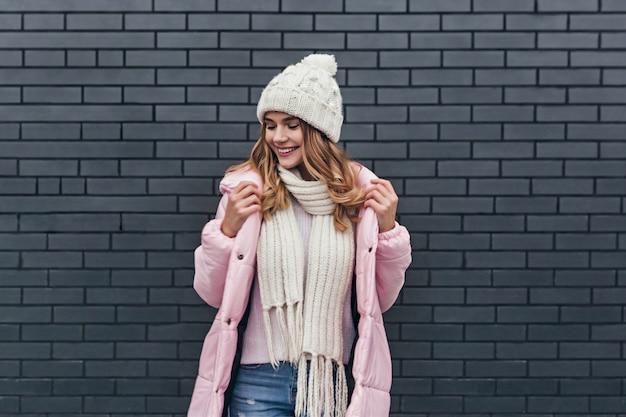 Fille incroyable avec un beau sourire appréciant la séance photo par matinée froide. modèle féminin blonde à la mode en manteau et bonnet tricoté posant près du mur de briques.