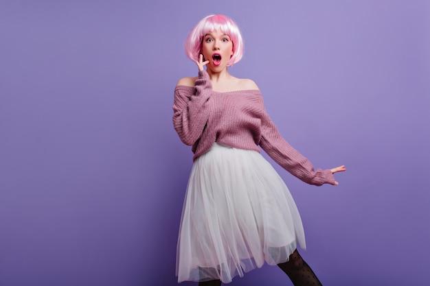 Fille incroyable en collants noirs et pull tricoté drôle posant sur le mur violet. enthousiaste jeune femme en perruque brillante exprimant des émotions surprises.