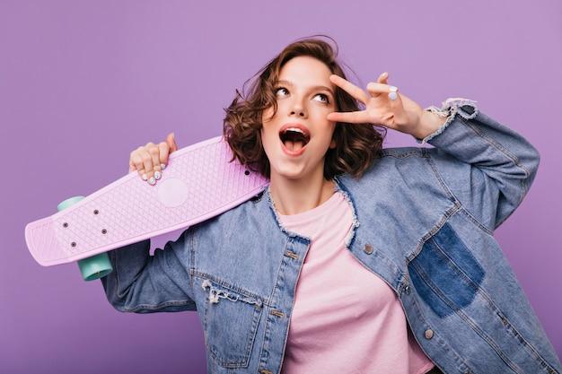 Fille incroyable ludique posant drôle. plan intérieur d'une jeune femme heureuse en veste en jean.