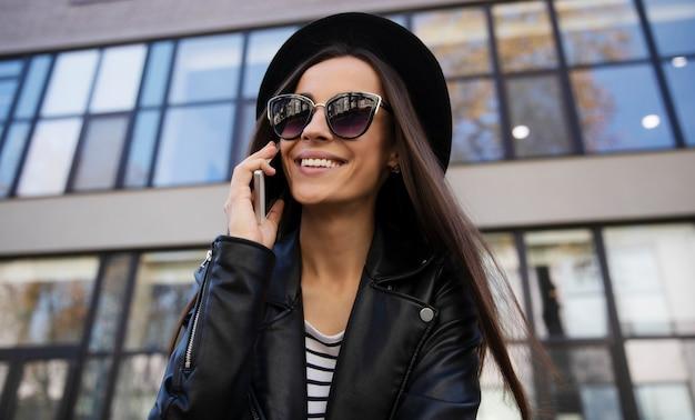 Une fille incroyablement belle dans des vêtements à la mode se tient près d'un immeuble de bureaux, souriant et riant en lisant quelque chose dans son smartphone