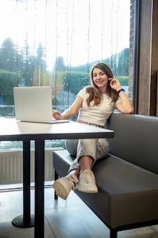 Fille indépendante souriante travaillant sur un ordinateur portable dans un café, journée de travail d'une jeune femme libre.