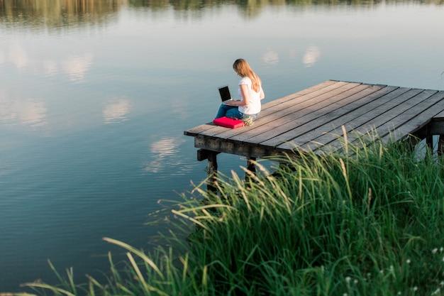 Fille indépendante travaillant avec un ordinateur portable à l'extérieur près de l'eau