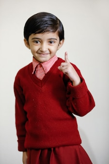 Fille indienne en uniforme scolaire et montrant le doigt