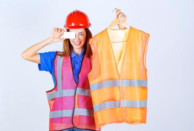 Fille ingénieur en uniforme présentant un morceau de veste de sécurité au collègue et présentant sa carte de visite.