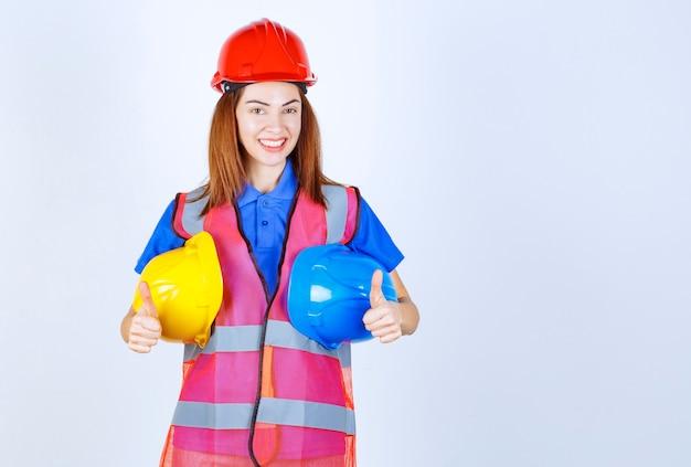 Fille ingénieur en uniforme tenant des casques bleus et jaunes et montrant le pouce vers le haut.