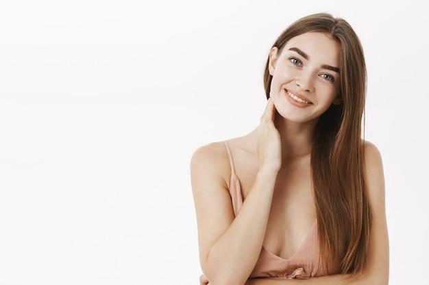 Fille innocente féminine tendre et attentionnée avec de longs cheveux bruns sains inclinant la tête flirty souriant doucement et touchant le cou se sentant timide et sensuel posant en robe beige