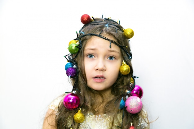 Fille inquiète avec des décorations de noël dans les cheveux.