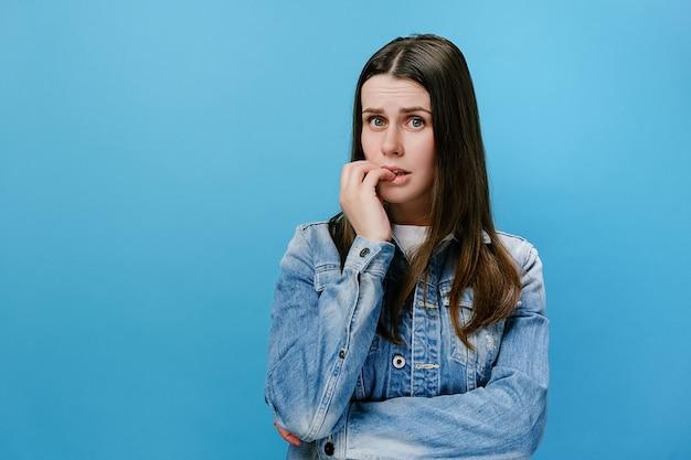 Une fille inquiète a joint les mains ensemble près de la bouche