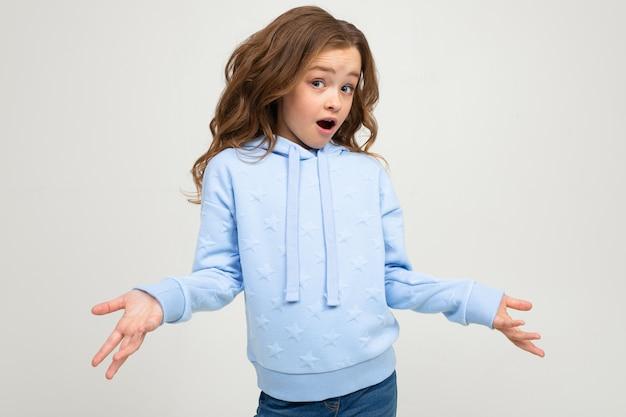 Fille insatisfaite dans un sweat à capuche bleu agitant les mains avec indignation sur un mur de studio de lumière