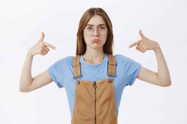 Fille insécurisée triste et sombre dans des lunettes pointant sur elle-même ou un logo, ressentant des regrets ou de la colère