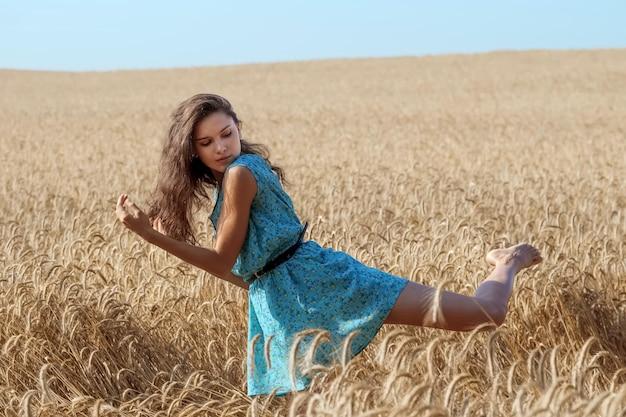 Fille insouciante dans une robe d'été bleue profite du soleil dans un champ de blé