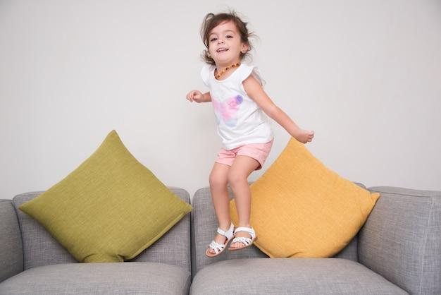 Une fille insouciante saute sur le canapé