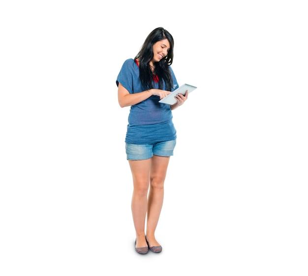 Une fille intelligente et décontractée utilisant sa tablette numérique en position debout