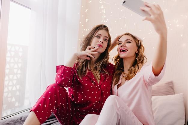 Fille intéressée en costume de nuit rouge à la recherche du téléphone d'un ami pendant qu'elle la prend en photo. heureuse femme blonde en pyjama rose à l'aide de smartphone pour selfie.