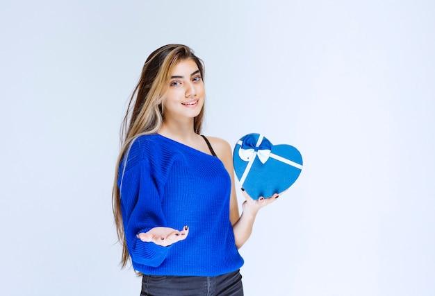 Fille invitant quelqu'un à présenter une boîte cadeau en forme de coeur bleu.