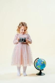 Fille sur un isolé tient un globe, une valise est debout à proximité