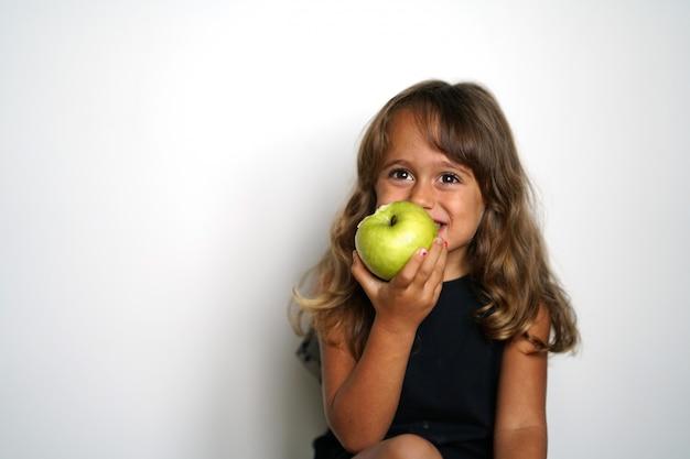 Fille italienne de 4 ans mange une pomme verte