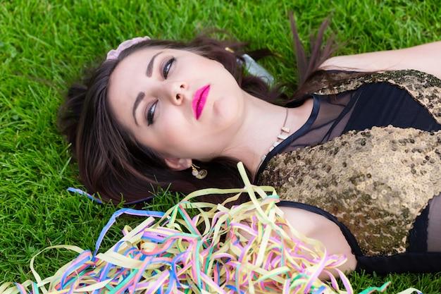 Fille ivre allongée sur la pelouse après une soirée entre célibataires
