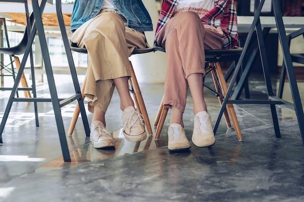 Fille, jambes, adolescent, porter, baskets, séance, parler, ensemble