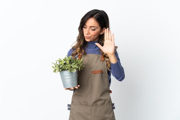 Fille de jardinier tenant une plante sur blanc faisant le geste d'arrêt et déçu
