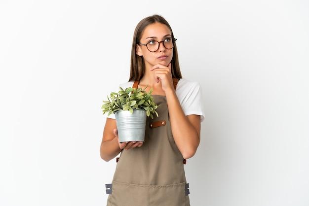 Fille de jardinier tenant une plante sur fond blanc isolé ayant des doutes