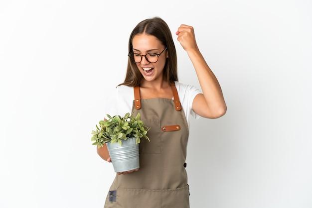 Fille de jardinier tenant une plante sur fond blanc isolé célébrant une victoire