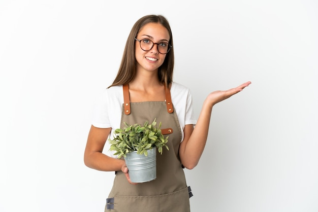Fille de jardinier tenant une plante sur fond blanc isolé étendant les mains sur le côté pour inviter à venir