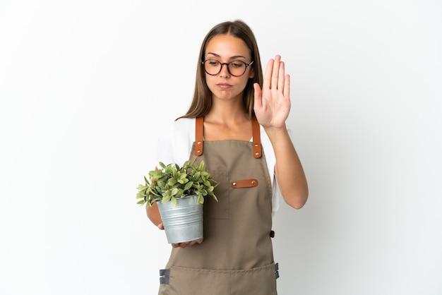 Fille de jardinier tenant une plante sur fond blanc isolé faisant un geste d'arrêt et déçu