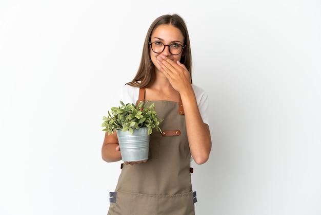 Fille de jardinier tenant une plante sur fond blanc isolé heureux et souriant couvrant la bouche avec la main