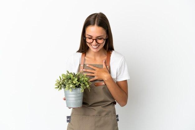 Fille de jardinier tenant une plante sur fond blanc isolé souriant beaucoup