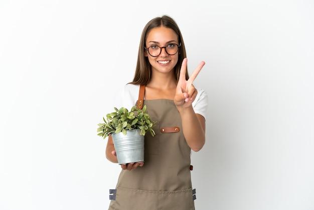 Fille de jardinier tenant une plante sur fond blanc isolé souriant et montrant le signe de la victoire