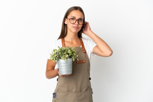 Fille de jardinier tenant une plante isolée ayant des doutes