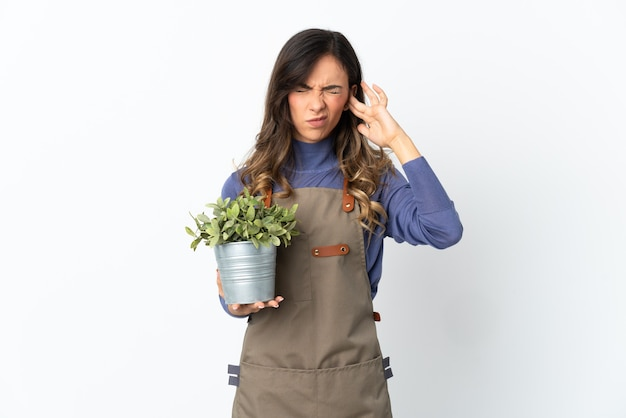 Fille de jardinier tenant une plante isolée sur un espace blanc frustré et couvrant les oreilles