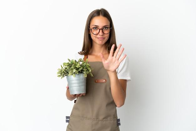 Fille de jardinier tenant une plante isolée sur fond blanc comptant cinq avec les doigts