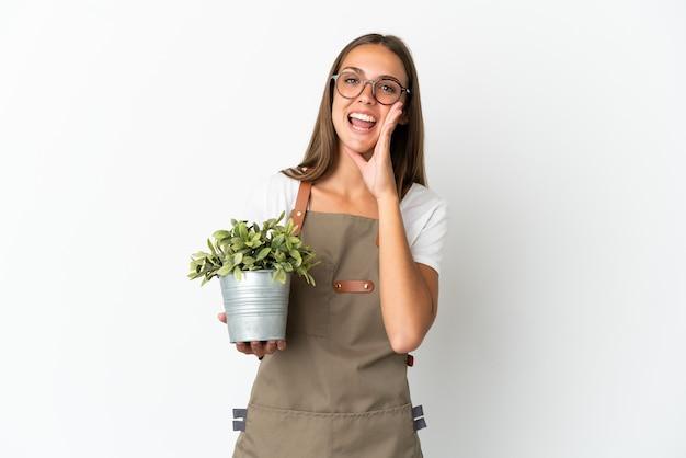 Fille de jardinier tenant une plante isolée sur fond blanc criant avec la bouche grande ouverte