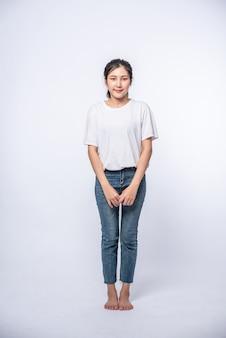 Fille en jean stretch blanc et debout sur une surface blanche.