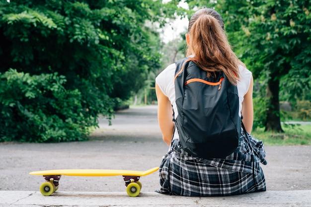 Fille en jean, tee-shirt et baskets, qui s'assied sur les marches à côté de son skateboard jaune