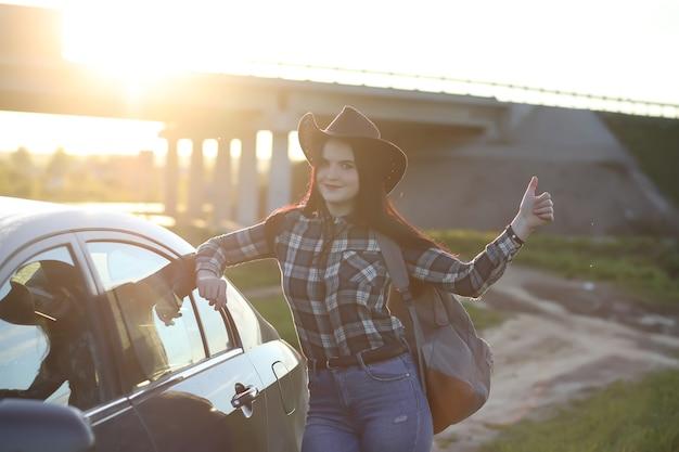 Une fille en jeans et chapeau parcourt l'été à la campagne