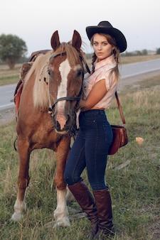 Fille en jeans chemise chapeau noir cowboy avec cheval