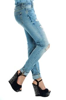Fille en jeans et talons hauts avec des clous et des strass